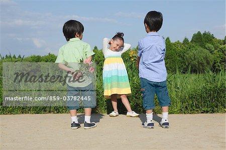 Boys Offering Flowers to Girl Stock Photo - Rights-Managed, Image code: 859-03782445