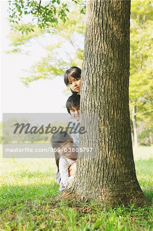 Children Hiding Behind Tree Trunk Stock Photo - Rights-Managed, Image code: 859-03805797