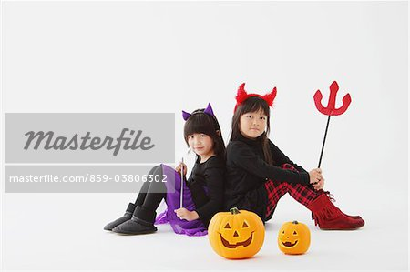 Two Girl Dressed In Halloween Costume Back To Back Stock Photo - Rights-Managed, Image code: 859-03806302