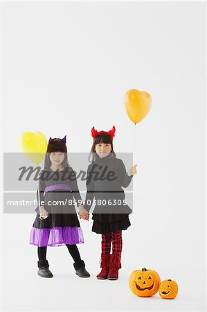 Two Girl Dressed In Halloween Costume Holding Balloons Stock Photo - Rights-Managed, Image code: 859-03806305