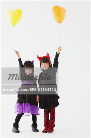 Two Girl Dressed In Halloween Costume Holding Balloons Stock Photo - Rights-Managed, Image code: 859-03806306