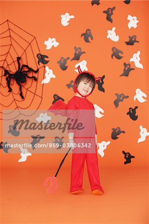 Boy Dressed Up As Devil against Orange Background Stock Photo - Rights-Managed, Image code: 859-03806342