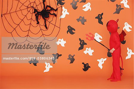 Boy Dressed Up As Devil against Orange Background Stock Photo - Rights-Managed, Image code: 859-03806343
