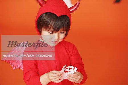 Boy Dressed Up As Devil against Holding Ghost Stock Photo - Rights-Managed, Image code: 859-03806346
