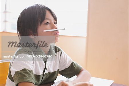 Boy Balancing Pencil Between Lips And Nose Stock Photo - Rights-Managed, Image code: 859-03860780