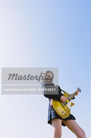 Japanese schoolgirl playing guitar in her uniform Stock Photo - Rights-Managed, Image code: 859-06404863