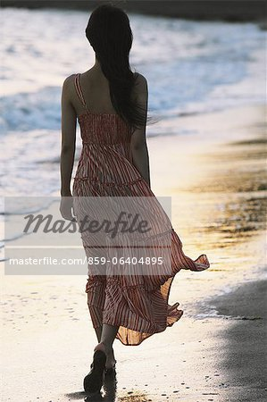 Japanese woman in a long dress walking away at the beach Stock Photo - Rights-Managed, Image code: 859-06404895