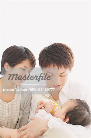 Young adult couple feeding milk from bottle to their baby Stock Photo - Rights-Managed, Image code: 859-06469777