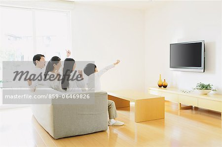 Family of four people watching TV on the sofa in the living room Stock Photo - Rights-Managed, Image code: 859-06469826