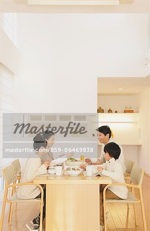 Family of four people eating at the dining table in the living room Stock Photo - Rights-Managed, Image code: 859-06469838