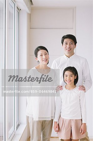 Mature adult couple with their daughter smiling at camera by the window Stock Photo - Rights-Managed, Image code: 859-06469841