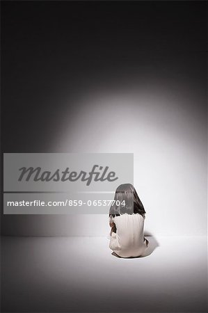 Sad girl in a white dress sitting on the floor against the wall Stock Photo - Rights-Managed, Image code: 859-06537704