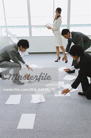 Business people picking up papers Stock Photo - Rights-Managed, Image code: 859-06538173