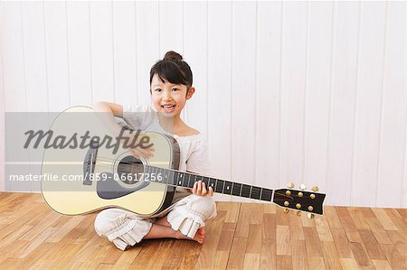 Girl Playing the Guitar Stock Photo - Rights-Managed, Image code: 859-06617256