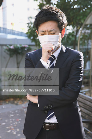 Sick Japanese young businessman in a suit at the park Stock Photo - Rights-Managed, Image code: 859-07711103