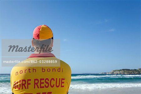 A lifesaver watches the surf on Bondi Beach in eastern Sydney. Lifesavers are a common sight on Australian beaches,assisting swimmers in distress. Stock Photo - Rights-Managed, Image code: 862-03288859