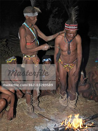 A bushman,or San,weeps in a trance as he is helped by members of his band during a sing-song round their campfire. The men have rattles wound round their legs to help the rest of them keep rhythm during their dances.These NS hunter gatherers live in the Xai Xai Hills close to the Namibian border. Their traditional way of life is fast disappearing. Stock Photo - Rights-Managed, Image code: 862-03289589
