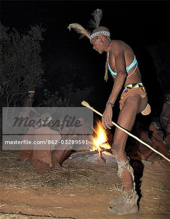 A bushman,or San,dances during a sing-song round their campfire. The men have rattles wound round their legs to help the rest of them keep rhythm during their dances.These NS hunter gatherers live in the Xai Xai Hills close to the Namibian border. Their traditional way of life is fast disappearing. Stock Photo - Rights-Managed, Image code: 862-03289591