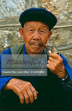 A Naxi man smokes his pipe Stock Photo - Rights-Managed, Image code: 862-03289880
