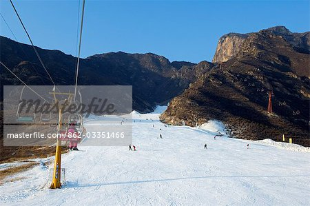 China,Beijing,Shijinglong ski resort. A ski lift taking skiers up to the slopes. Stock Photo - Rights-Managed, Image code: 862-03351466