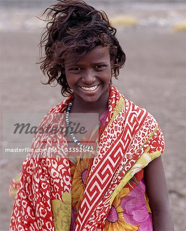 A pretty tousle-haired girl of the nomadic Afar tribe wears bright colours in stark contrast to the drab,windswept surroundings of Lake Abbe. Stock Photo - Rights-Managed, Image code: 862-03352642