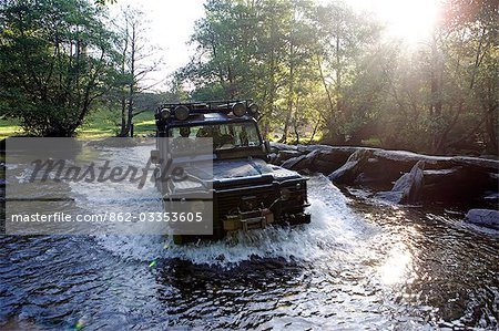 England,Somerset,Exmoor. The ford at Tarr Steps is waded by a four wheel drive - a Landrover Defender 110 with the prehistoric clapper bridge on the right hand side. Stock Photo - Rights-Managed, Image code: 862-03353605