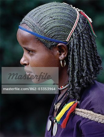 A young Ethiopian girl with unusual braided hair; the crown of her head has been smeared with a greenish substance. Her two pendants are made from Maria Theresa thalers old silver coins minted in Austria,which were widely used as currency in northern Ethiopia and Arabia until the end of World War II. Stock Photo - Rights-Managed, Image code: 862-03353964