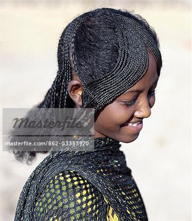 The fetching hairstyle of a young Afar girl. Proud and fiercely independent,the nomadic Afar people live in the low-lying deserts of Eastern Ethiopia. Stock Photo - Rights-Managed, Image code: 862-03353970