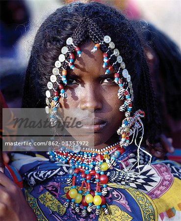 An Afar girl has her attractive hairstyle embellished with buttons and beads,which is typical of the young girls of her tribe. Proud and fiercely independent,the nomadic Afar people live in the low-lying deserts of Eastern Ethiopia. Stock Photo - Rights-Managed, Image code: 862-03353972