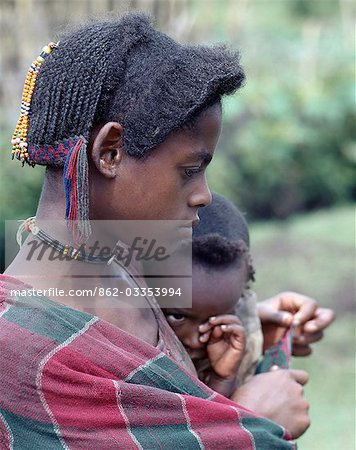 A young mother and child of the Arsi-Oromo people west of Aje. Both have unusual hairstyles. The braids falling from the crown of the mother's head have been attractively woven with wool to make a colourful fringe. Stock Photo - Rights-Managed, Image code: 862-03353994