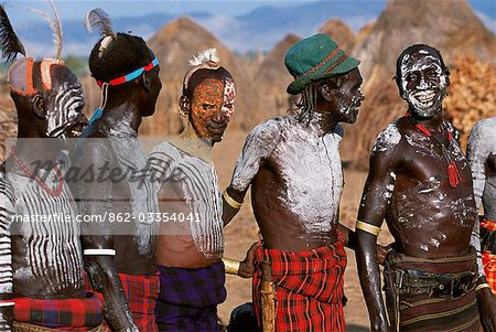 At a dance in the Karo village of Duss men stand waiting to dance. A small Omotic tribe related to the Hamar,the Karo live along the banks of the Omo River in southwestern Ethiopia. They are renowned for their elaborate body art using white chalk,crushed rock and other natural pigments. Stock Photo - Rights-Managed, Image code: 862-03354041