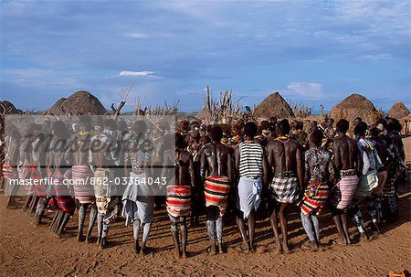 The men hold hands forming a circle within which the women dance in the Karo village of Duss. A small Omotic tribe related to the Hamar,the Karo live along the banks of the Omo River in southwestern Ethiopia. They are renowned for their elaborate body art using white chalk,crushed rock and other natural pigments. Stock Photo - Rights-Managed, Image code: 862-03354043