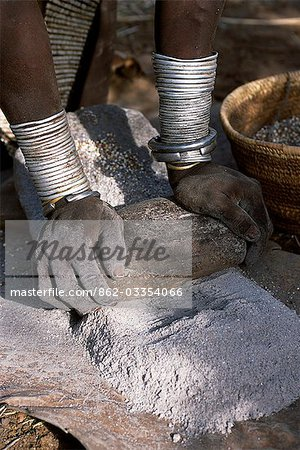A Nyangatom woman grinds sorghum using two stones. Typical of her tribe,she wears a heavily beaded calfskin skirt,multiple layers of bead necklaces and metal bracelets and amulets. The Nyangatom or Bume are a Nilotic tribe of semi-nomadic pastoralists who live along the banks of the Omo River in south-western Ethiopia. Stock Photo - Rights-Managed, Image code: 862-03354066