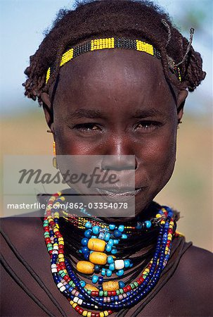 A young Dassanech girl wears a beautiful array of beaded necklaces. Much the largest of the tribes in the Omo Valley numbering around 50,000,the Dassanech (also known as the Galeb,Changila or Merille) are Nilotic pastoralists and agriculturalists. Stock Photo - Rights-Managed, Image code: 862-03354078