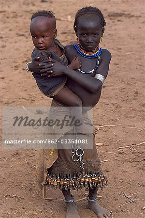 A young Dassanech girl holds her little brother. She wears a leather skirt with an elaborate fringe of wooden and metal tassles. Much the largest of the tribes in the Omo Valley numbering around 50,000,the Dassanech (also known as the Galeb,Changila or Merille) are Nilotic pastoralists and agriculturalists. Stock Photo - Rights-Managed, Image code: 862-03354081