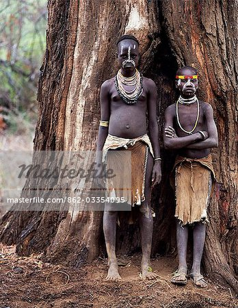 Two young Karo girls stand in front of the massive trunk of a fig tree. A small Omotic tribe related to the Hamar,who live along the banks of the Omo River in southwestern Ethiopia,the Karo are renowned for their elaborate body painting using white chalk,crushed rock and other natural pigments. Stock Photo - Rights-Managed, Image code: 862-03354095
