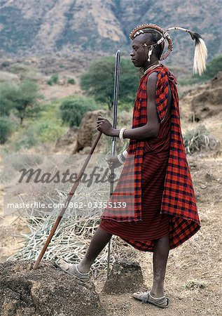 A Maasai warrior with his hair styled in a most unusual way. His long braids have been wrapped tightly in leather,decorated with beads and tied in an arch over his head. A colobus monkey tail sets this singular hairstyle apart from the more traditional warrior styles. Stock Photo - Rights-Managed, Image code: 862-03355139
