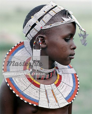 A Maasai girl in traditional attire. The predominant white colour of her beadwork and the circular scar on her cheek denote that she is from the Kisongo section of the Maasai,the largest clan group,which lives either side of the border in Kenya and Tanzania. Stock Photo - Rights-Managed, Image code: 862-03355141