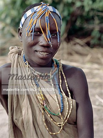 A Hadza girl wearing a beaded headband and necklaces.The Hadzabe are a thousand-strong community of hunter-gatherers who have lived in the Lake Eyasi basin for centuries. They are one of only four or five societies in the world that still earn a living primarily from wild resources. Stock Photo - Rights-Managed, Image code: 862-03355175