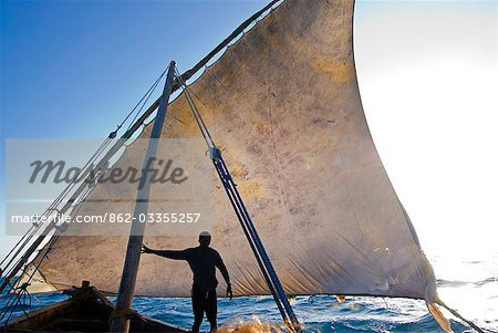 East Africa,Tanzania. Sailing an Arab dhow in Zanzibar. A dhow is a traditional Arab sailing vessel with one or more lateen sails. It is primarily used along the coasts of the Arabian Peninsula,India,and East Africa. Stock Photo - Rights-Managed, Image code: 862-03355257