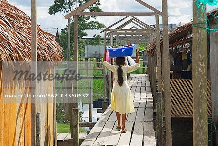 Peru,Amazon River. Indigenous Indian girl carrying her washing in the village of Islandia. Stock Photo - Rights-Managed, Image code: 862-03360632