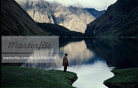 A high lake in the Vilcabamba range; at the waters edge a mule wrangler checks his fishing line at dawn. Stock Photo - Rights-Managed, Image code: 862-03360705