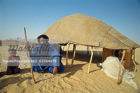 Blue clad Tuareg male elder and grand children outside his reed woven shelter Stock Photo - Rights-Managed, Image code: 862-03364070