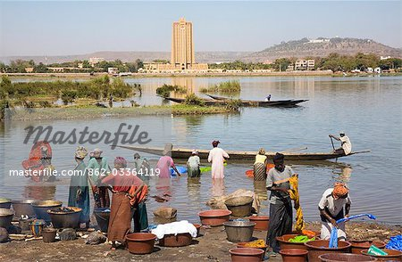 Mali,Bamako. Dyeing and rinsing cotton cloth on the outskirts of Bamako with the imposing Bank of West Africa building dominating the skyline on the opposite bank of the Niger River. Stock Photo - Rights-Managed, Image code: 862-03364119