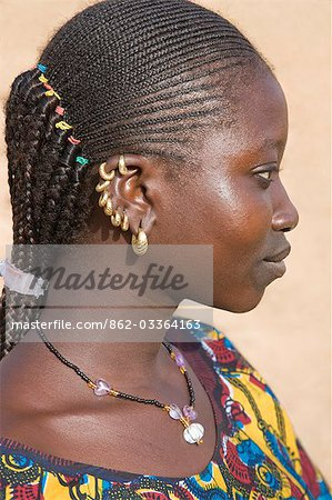Mali,Douentza. A Bella woman with braided hair wearing gold ear rings in her village near Douentza. The Bella are predominantly pastoral people and were once the slaves of the Tuareg of Northern Mali. Stock Photo - Rights-Managed, Image code: 862-03364163