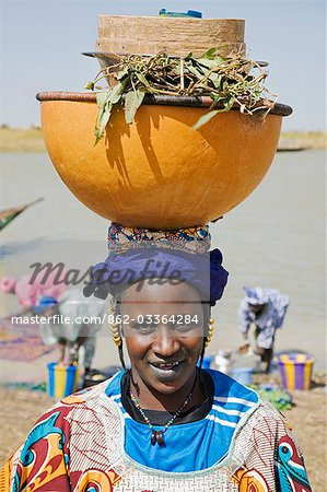 Mali,Tupe,Niger Inland Delta. A woman with gold hair ornaments leaves the Niger River with a headload of cooking pots and utensils. Her facial markings and the light tattooing round her lips indicate that she is from the Peul tribe. Stock Photo - Rights-Managed, Image code: 862-03364284
