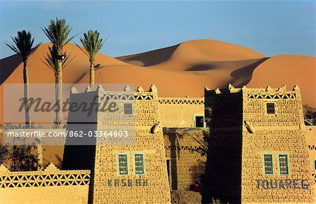 A desert kasbah backing onto the giant sand dunes of Erg Chebbi in eastern Morocco.
