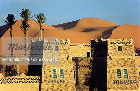 A desert kasbah backing onto the giant sand dunes of Erg Chebbi in eastern Morocco.