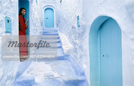 A local woman steps out into the whitewashed streets of the Rif Mountains town of Chefchaouen. The distinctive white and blue colour scheme was first introduced by Jewish refugees fleeing Spain in the 15th century. Stock Photo - Rights-Managed, Image code: 862-03364804