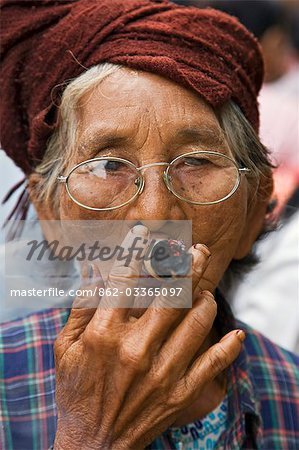 Myanmar. Burma. Nyaung U. An old bespectacled woman smokes a local cheroot in Nyaung U market. Stock Photo - Rights-Managed, Image code: 862-03365097
